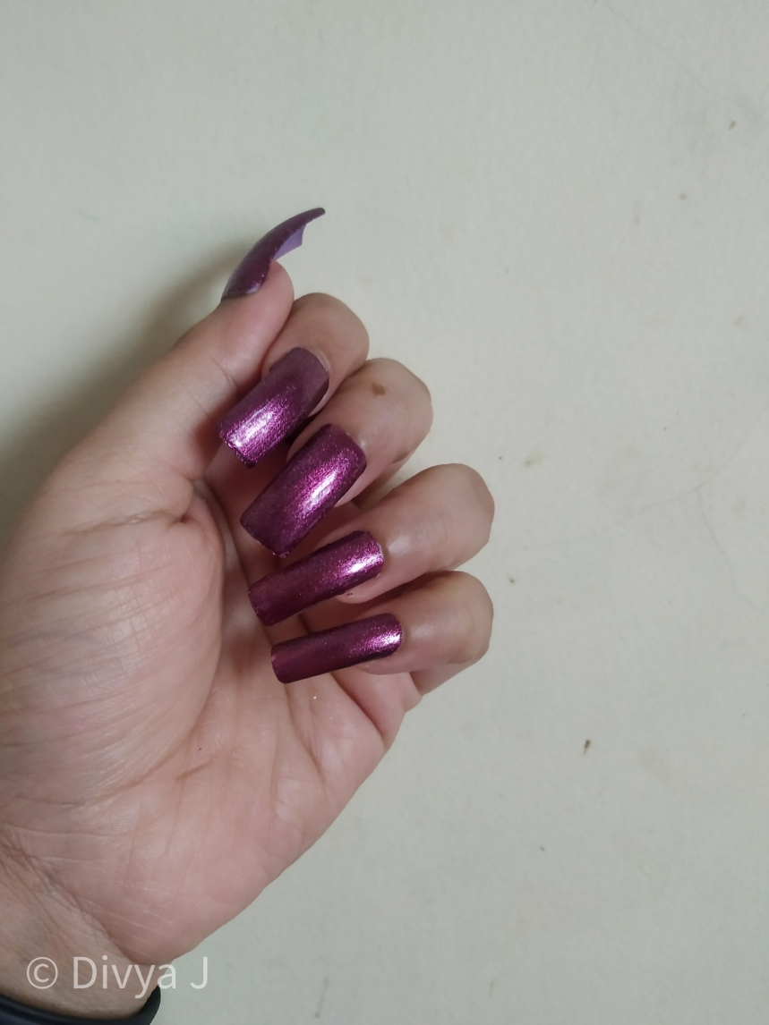 Hand swatch of Kyth and kin metallic nail lacquer Purple Haze in Artificial Light