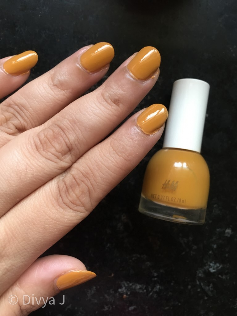 Hand and bottle shot of H&M Golden Turmeric nail polish